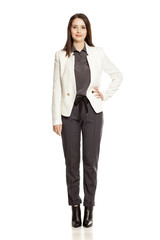 Young businesswoman  in pants and suit standing on white background