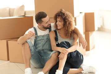 smiling couple on the background of large cardboard boxes.