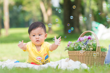 Asia Baby boy sitting on green grass with soap bubbles