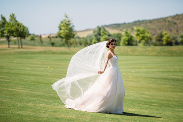 Beautiful bride in luxury fashion white wedding dress with veil on the green golf club glade, wedding day. Amazing full length body portrait of girl. Marriage concept.