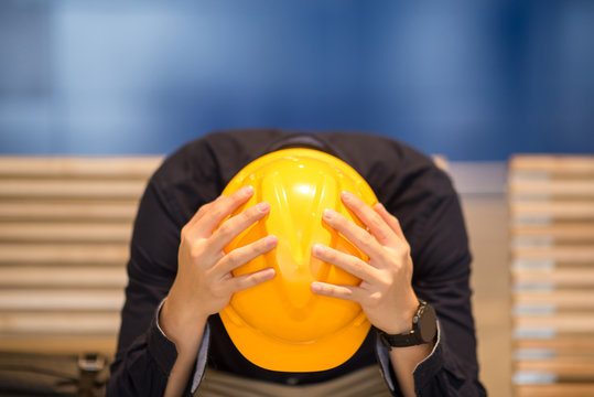 Young Asian engineer or architect man feeling tried and worried while sitting on bench holding his personal yellow protective safety helmet. depression from hard work concept