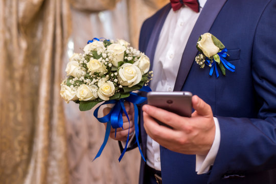 the groom is holding a phone and a bouquet of the bride