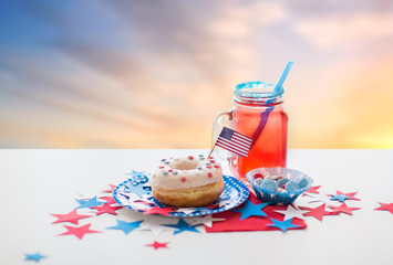american independence day, celebration, patriotism and holidays concept - close up of glazed donut decorated with flag, drink in mason jar and candies at 4th july party over evening sky background