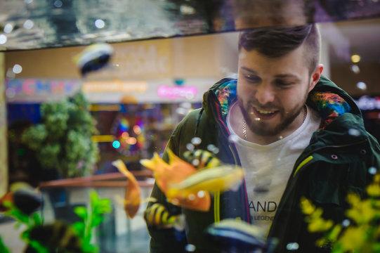 man looks at tropical fish in aquarium