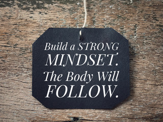 Motivational and inspirational quote - Build a strong mindset. The body will follow. With vintage styled background.