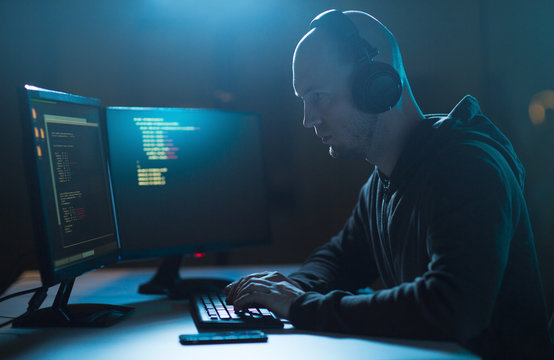 cybercrime, hacking and technology concept - male hacker with headphones and coding on laptop computer screen wiretapping or using computer virus program for cyber attack in dark room