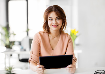 business, technology and people concept - smiling businesswoman with tablet pc computer working at office