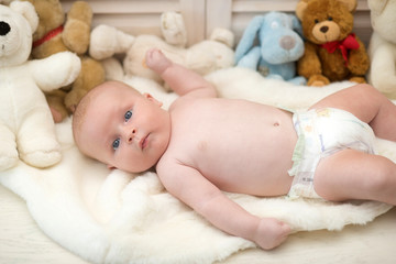 Infant with blue eyes and curious face on light blanket
