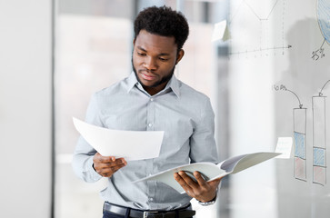 business, people and corporate concept - african american businessman with folder at office