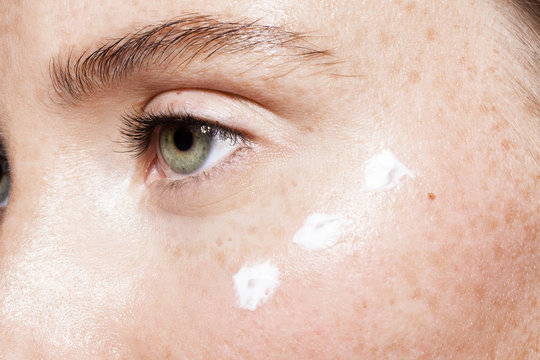 Close up of woman's face with moisturizer