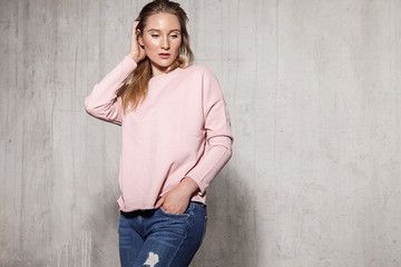 Portrait of young blonde in stylish clothes touching her nice hair and looking down with sensitivity. Attractive girl standing in pink jersey and casual jeans. Copy space in right side