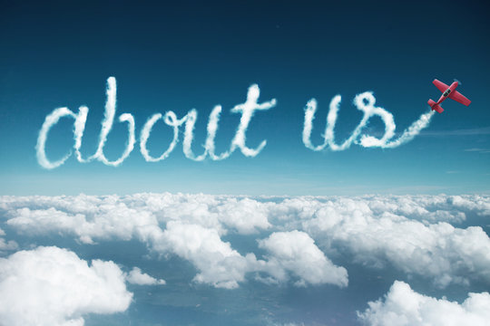 about us word created from a trail of smoke by Acrobatic plane.