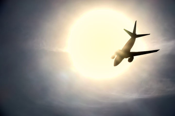 The silhouette of a jet plane flying into the sun. Concept for traveling to hot tropical countries.
