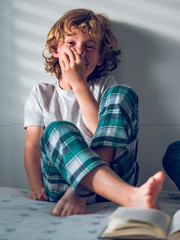 Boy smelling foot on bed