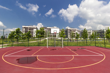 Colourful basketball court outdoors in a bright springtime day, no people are visible