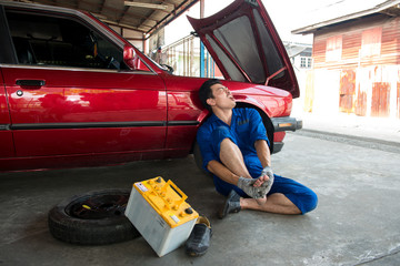 Asian mechanic get Injury and suffering at foot from battery car in garage. Foot Pain ,young man sitting on the floor at garage, he holding feet press massage. Incident case in the garage.