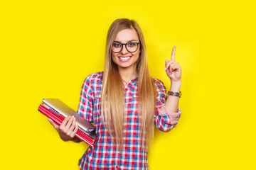 Smiling young stylish student is standing with books on yellow background in glasses and casual bright outfit