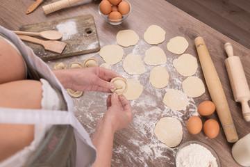 Preparing, cooking, making homemade ravioli, pelmeni or dumplings with meat