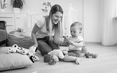 Black and white photo of adorable toddler boy playing on floor with his mother