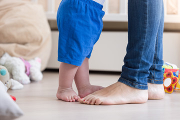 Closeup image of 10 months old baby boy's feet standing with mother