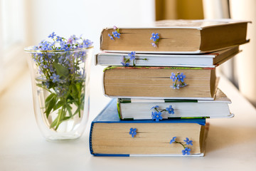 A stack of books with small blue flowers between pages on white table Wall mural