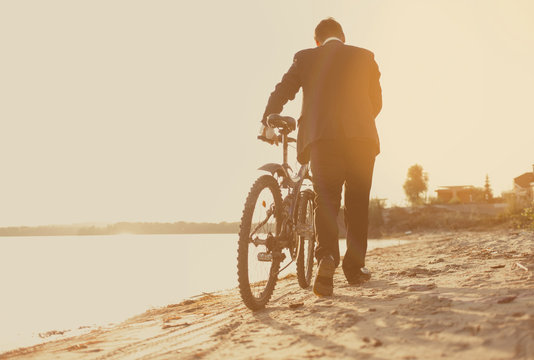 Businessman with a bicycle on the beach. Back view