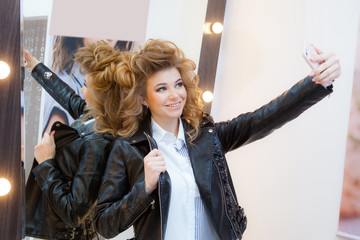 Young woman taking a self portrait photo for social networks after applying makeup in professional beauty salon.