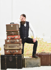 Macho elegant on disappointed face standing near pile of vintage suitcase. Man, butler with beard and mustache delivers luggage, luxury white interior background. Luggage and travelling concept.