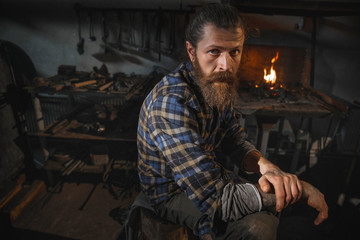 Portrait of a real Brutal blacksmith of a man with a beard after working in his workshop against the background of a burning flame. Portrait of a profession.