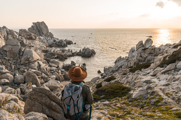 Italy, Sardinia, back view of hiker with backpack looking to the sea