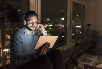 Businessman sitting on window sill in office at night using tablet and headphones
