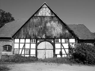 Altes Bauernhaus mit Fachwerk und großem Holztor bei Sonnenschein auf dem Lande in Hagen bei Lage im Kreis Lippe in Ostwestfalen, fotografiert in traditionellem Schwarzweiß