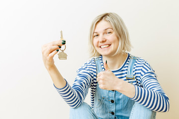 Image of woman with keys from apartment against blank wall