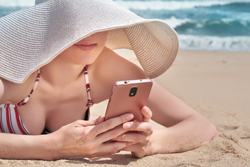 Beautiful woman using her smartphone data while relaxing on beach