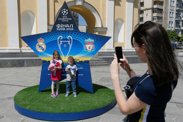A woman takes a picture of children in front of the logo of the Champions League Final at the Independence Square in Kiev