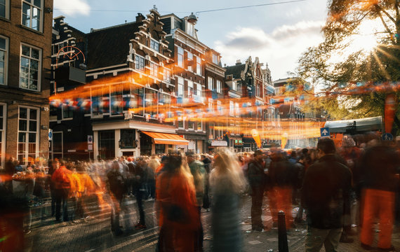 Streets of Amsterdam full of people in orange during the celebration of kings day. Blurred people at sunset with sunlight and orange decorations.