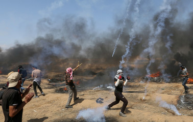 Tear gas canisters are fired by Israeli forces at Palestinian demonstrators during a protest demanding the right to return to their homeland, at the Israel-Gaza border in the southern Gaza Strip