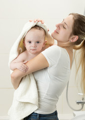 Portrait of young mother wiping her baby boy with big towel after having shower