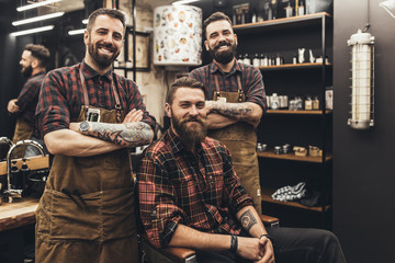 Hipster young good looking man visiting hairstylist and barber in barber shop.
