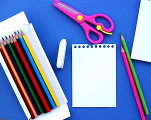 Stationery for school on a blue background. Notepad, a set of colored pencils, scissors, an eraser