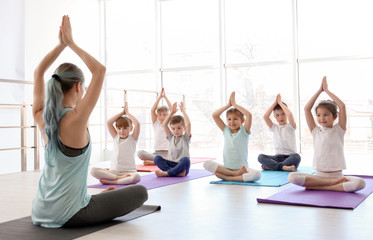 In de dag School de yoga Little children and their teacher practicing yoga in gym