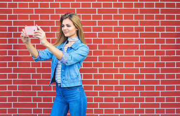 Young pretty woman taking selfie outdoors - Female summer fashion portrait - Teenager student holding mobile phone for selfi photo next to brick wall background