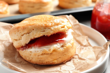 Tasty scone with clotted cream and jam on plate, closeup