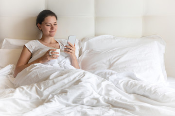 Portrait pretty young girl with smart phone on bed in modern apartment in the morning