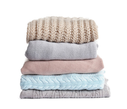 Stack of warm knitted clothes on white background