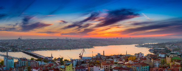Long exposure panoramic cityscape of Istanbul at a beautiful dramatic clouds sunset from Galata to Golden Horn gulf. View of the wonderful romantic old town at Sea of Marmara. Istanbul. Turkey.