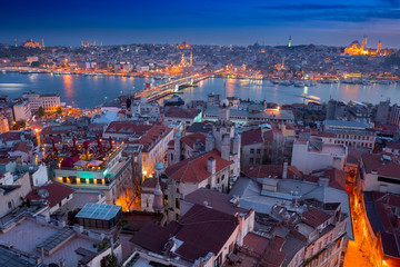 Long exposure panoramic cityscape of Istanbul at a warm calm evening from Galata to Golden Horn gulf. Wonderful romantic old town at Sea of Marmara. Bright light of street lighting. Istanbul. Turkey.