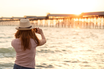 Young asian woman in hat is taking sunset beach photo with smartphone.