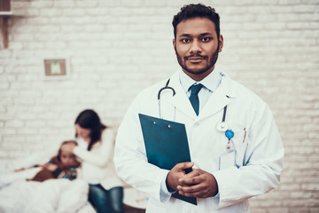 Indian doctor seeing patients at home. Doctor is posing with clipboard with pregnant mother and daughter in background.