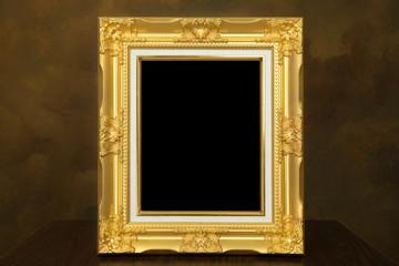 golden vintage frame on wooden table over gold background